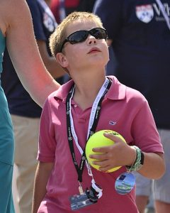 kid with tennis ball wearing sunglasses.
