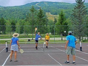 family playing outdoor pickleball